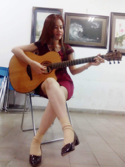 Vietnamese woman playing the guitar sitting in chair in art gallery.